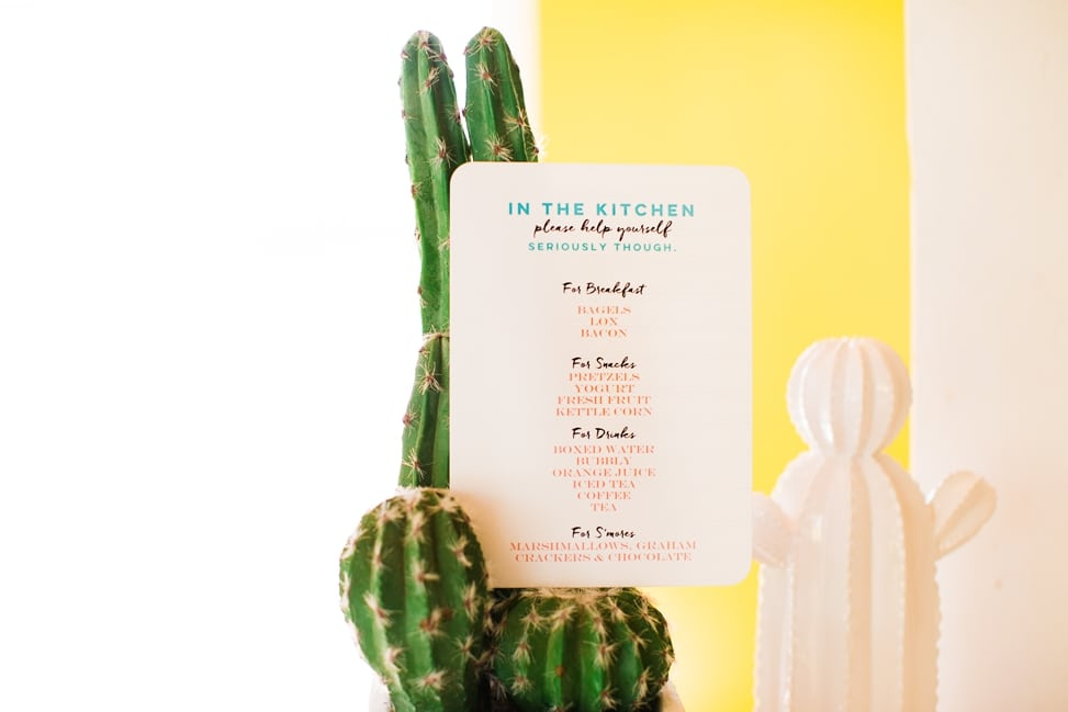 "a full color printed card with rounded edges that reads ""In the Kitchen"" and details food available for snacking. the sheet sits on a small cactus in front of a yellow wall"