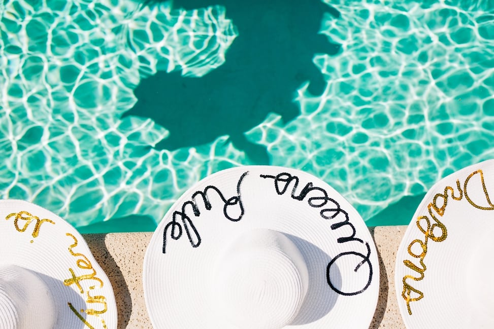 "Three sun hats at the edge of a pool—the middle one reads ""Queens Rule"" and there is a shadow of a dragon on the bottom of the pool"