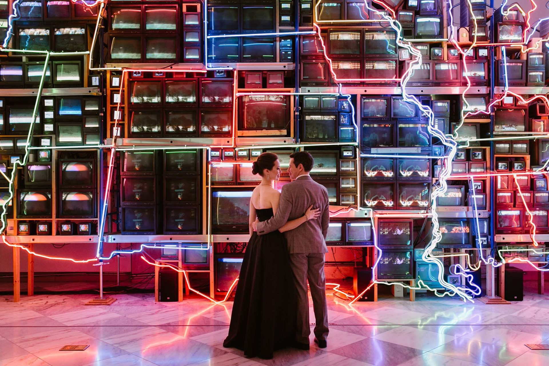 a couple stands in front of a neon sign installation of a map of the USA overlaying old TVs. Rachel Couch for Pop! Wed Co.