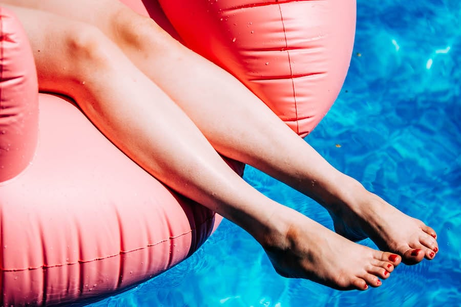 close up of women's legs and feet hanging off of pink flamingo floatie in blue pool