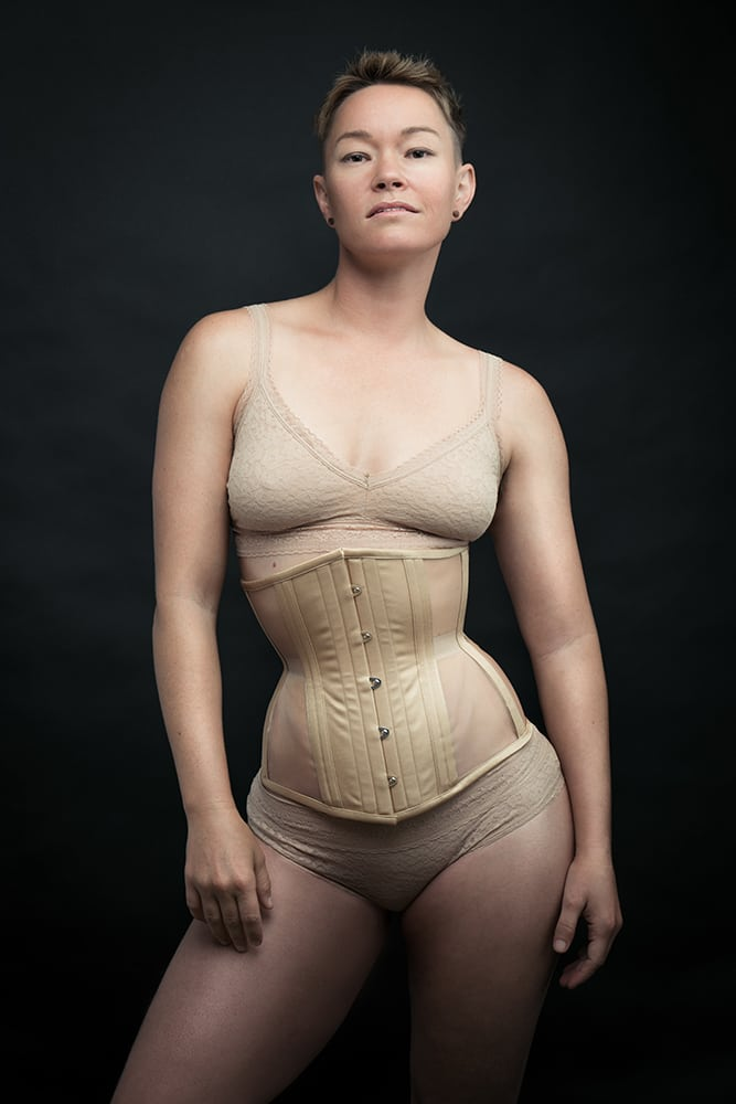 a gender nonconforming person wearing a skin-tone corset from Dark Garden with skin-tone bralette and knickers