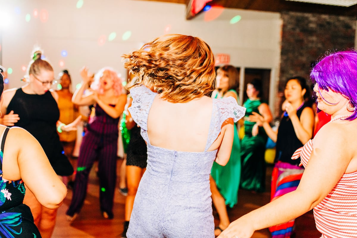 Women in party clothes shaking it off on the dance floor
