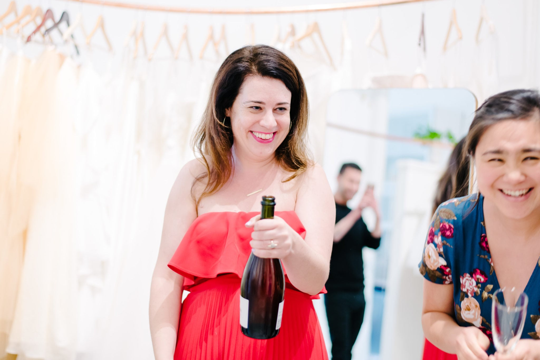 woman with long brunette hair wearing red dress is smiling holding champagne bottle woman beside her wearing blue floral dress is smiling holding champagne flute mirror behind women shows man dressed in black taking a picture with camera phone