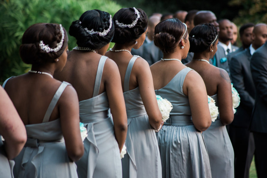 Five African-American bridesmaids with their hair up wearing light grey dresses and holding bouquets standing in a row with their backs to you during a wedding ceremony