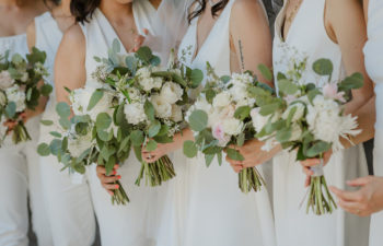 Women in all white sleeveless dresses and jumpsuits, holding bouquets