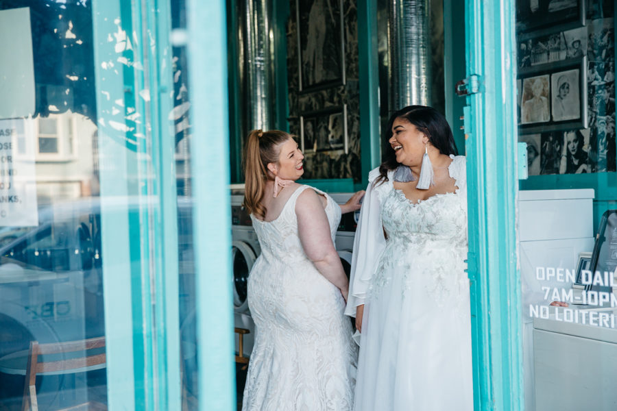 Two women in plus size wedding dresses from Lace & Liberty laughing in a teal doorway