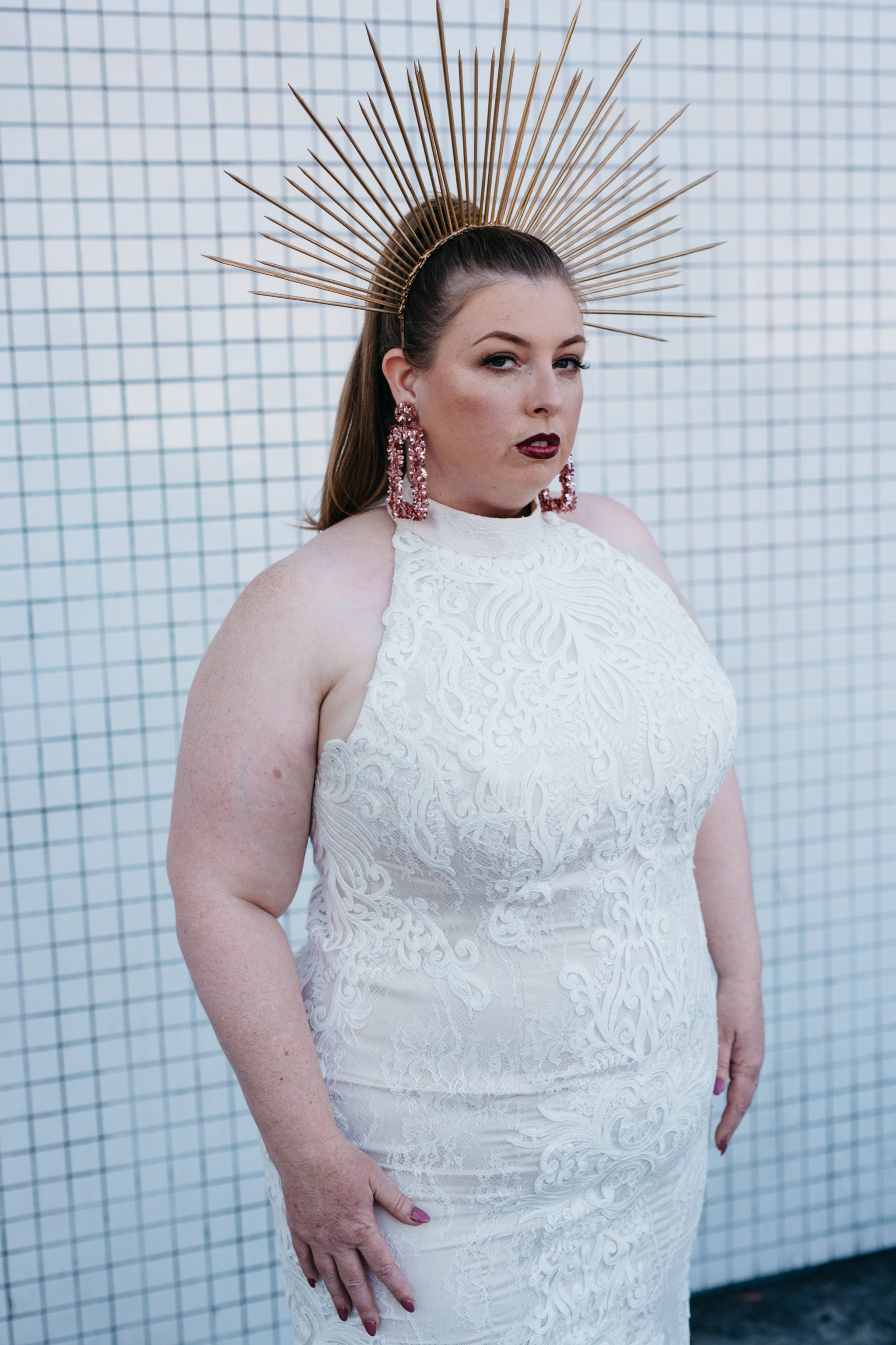 A woman with dark makeup and a radiant crown wearing a white lace halter plus size wedding dress from Lace and Liberty stands in front of a white tile wall