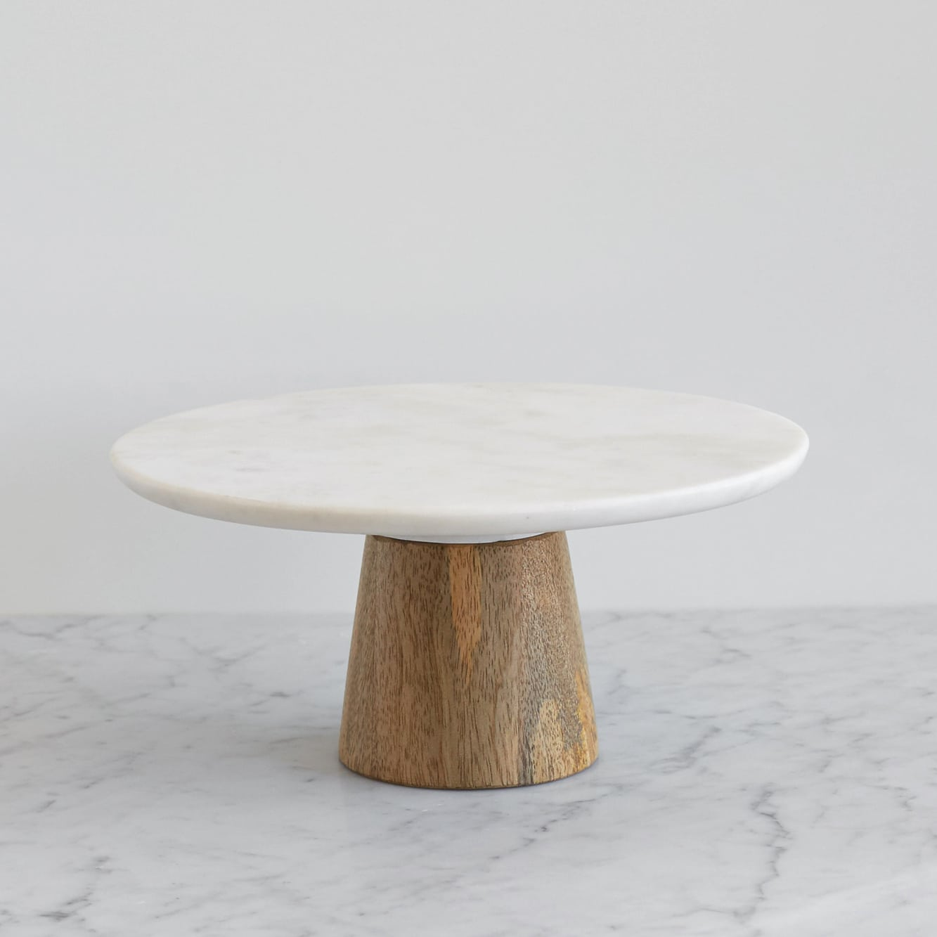 a marble cake stand with a wood base