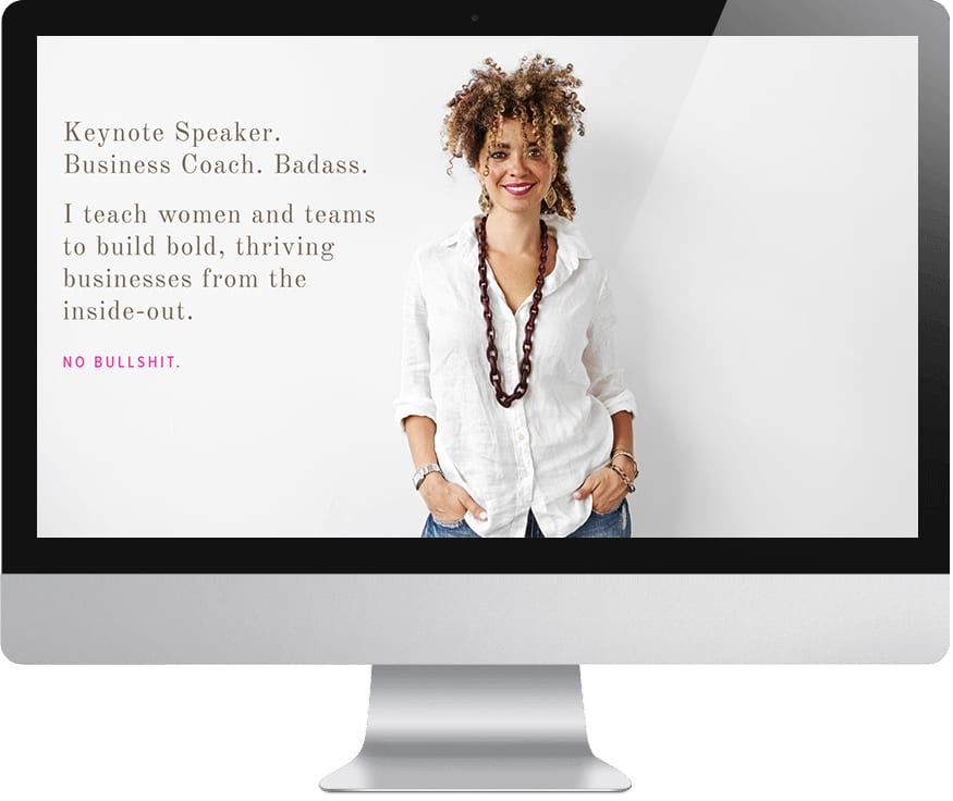 "Cyndie Spiegel's Squarespace Website with an image of Cyndie in a casual white button down shirt and a large necklace on a mac-style computer monitor. The text reads: ""Keynote Speaker. Business Coach. Badass. I teach women and teams to build bold, thriving businesses from the inside-out. No bullshit."""