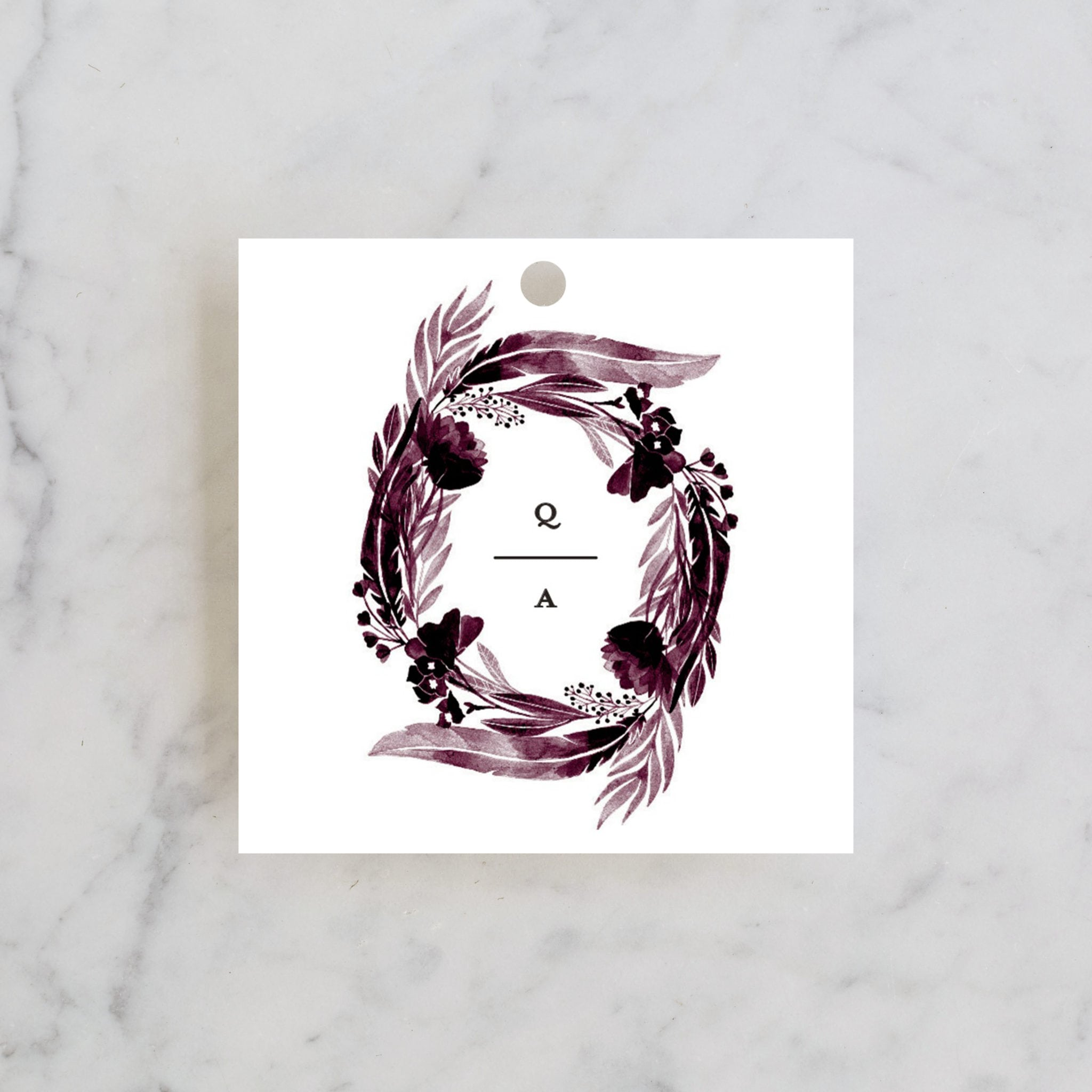 a wedding favor tag with a plum colored father wreath design and the letters Q|A