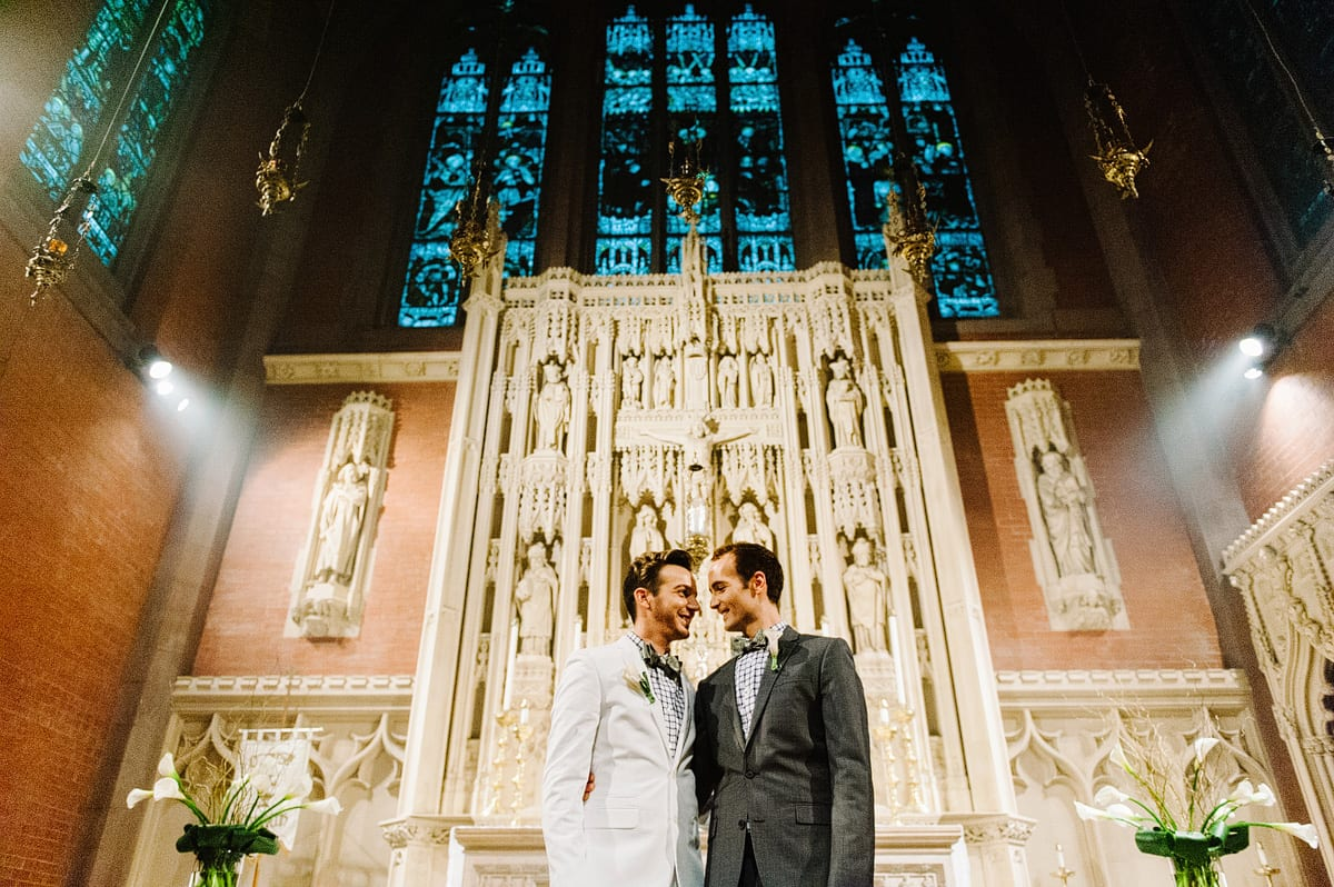 Kelly Prizel photo of two grooms standing in front of a dramatic church altar.