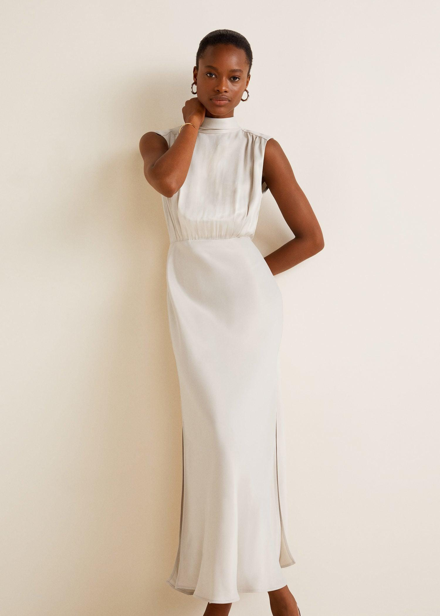 black woman with short hair wearing a high neck ivory satin gown