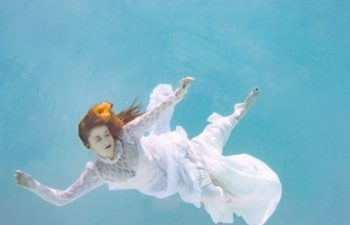 A red-headed woman in a wedding dress, floating, submerged in a blue swimming pool