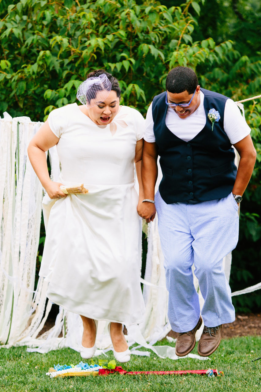 Kelly Prizel photo of a couple jumping over a broom during their wedding ceremony.