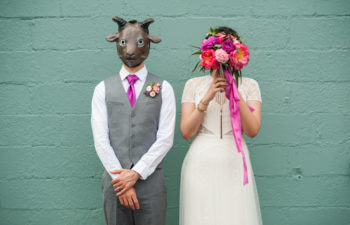 A bride and groom in wedding clothes stand in front of a teal wall. The groom wears a goat mask and the bride holds her brightly colored bouquet in front of her face.