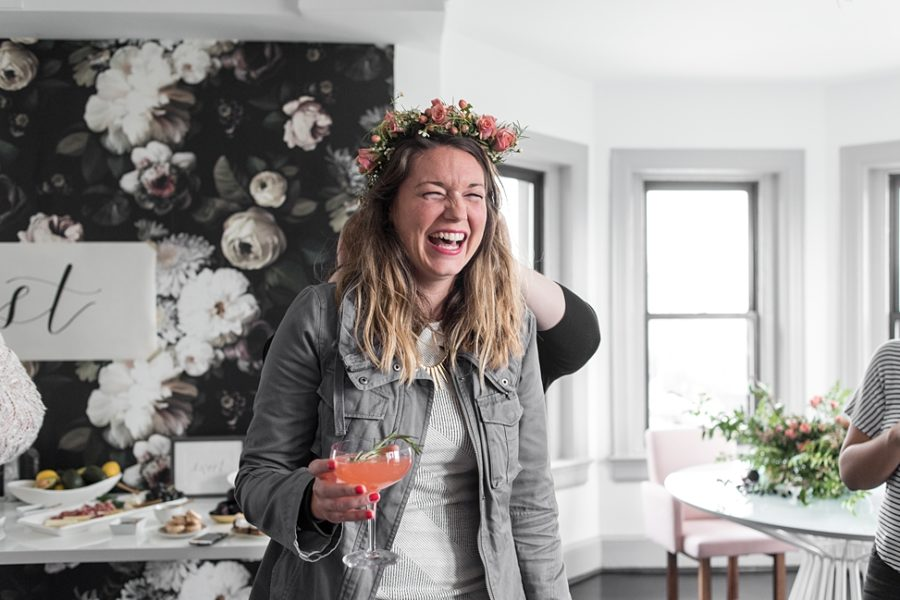 A woman holding a large pink cocktail laughs while her flower crown is adjusted by someone standing behind her in BUREAU's lounge area