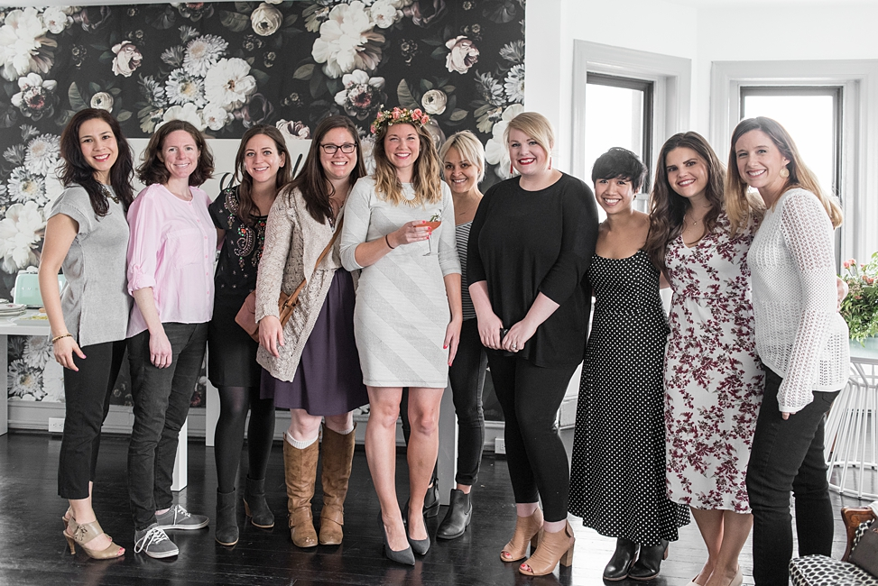 A large group of women look at you, posing for a picture at the Toast-themed shower at Bureau co-working and event space