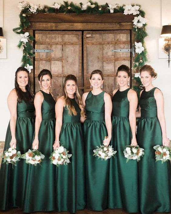 Group of women wearing winter wedding colors: dark green dresses and holding bouquets with greenery, white flowers, and pinecones