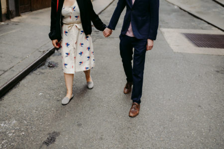 A woman in a white floral print dress with a black sweater holds hand with a man in a black suit on a grey street