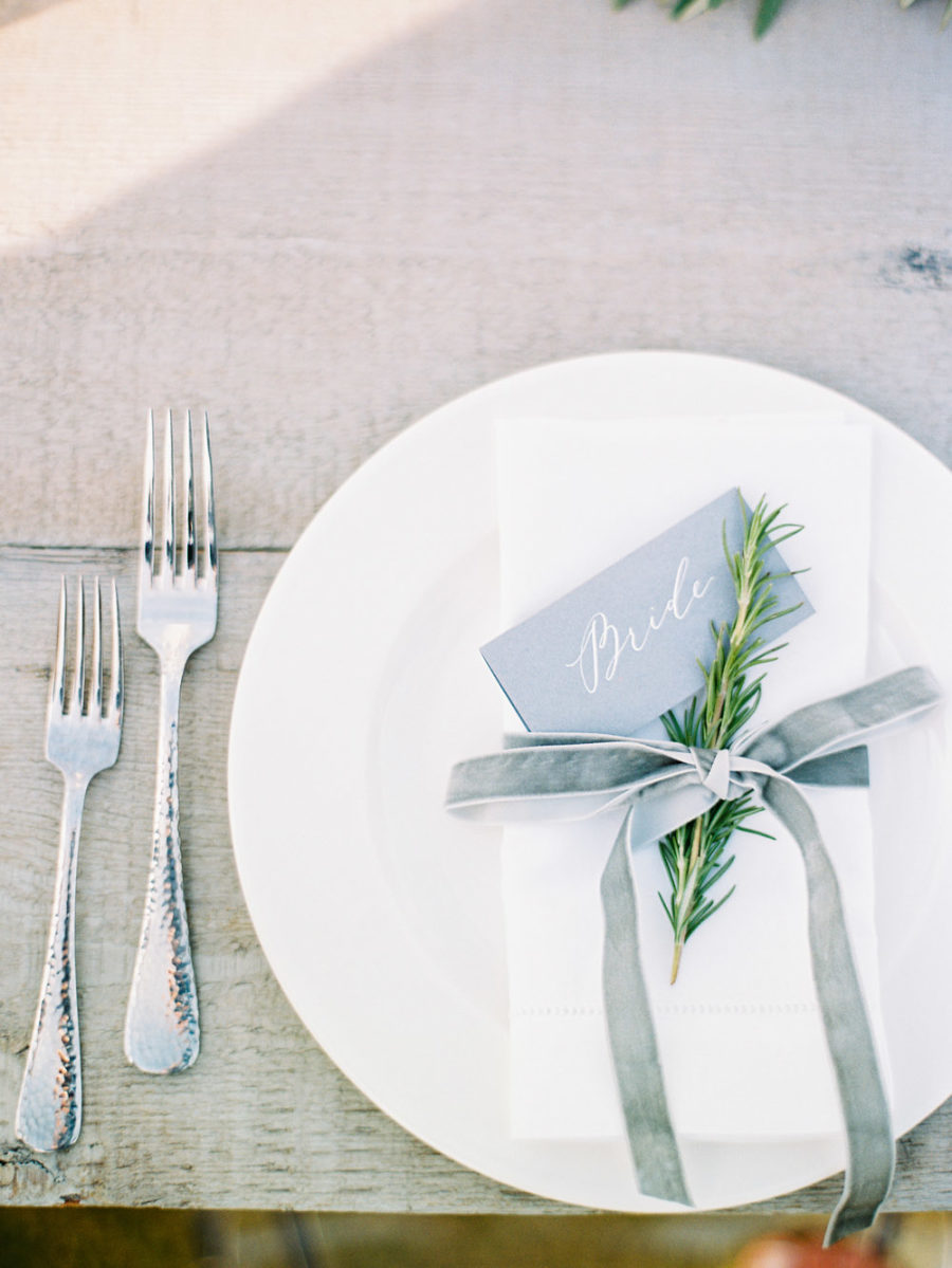 Table setting using winter wedding colors: grey place card, green rosemary sprig, and grey velvet ribbon