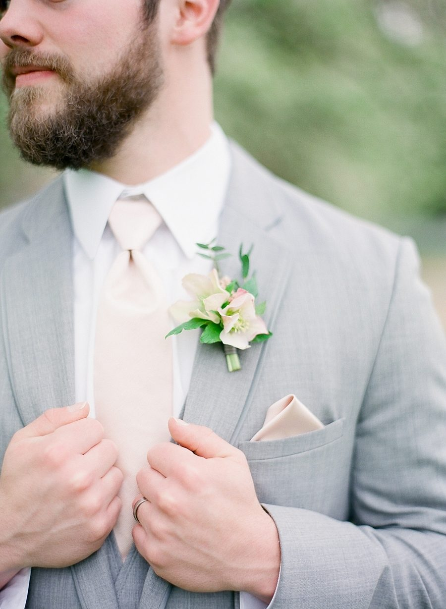 Closeup of man wearing winter wedding colors: a cream tie with grey suit