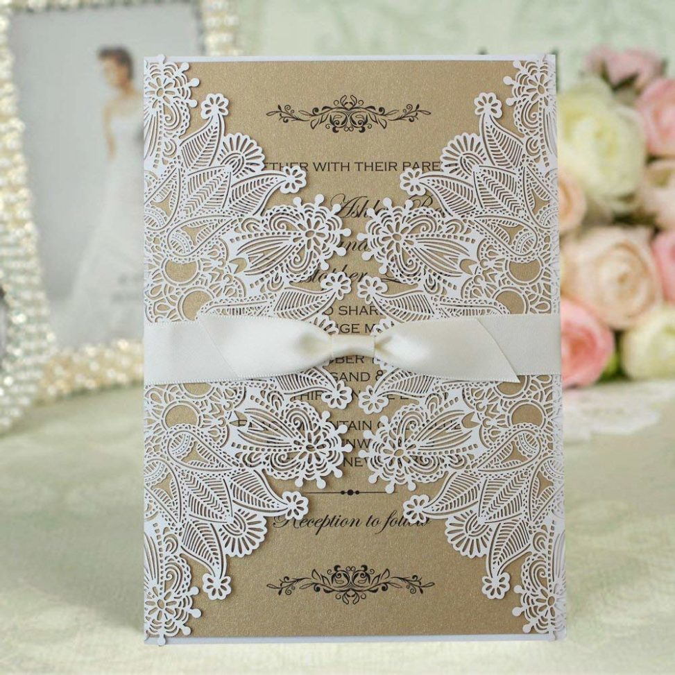 Winter wedding ideas for an invitation with lace overlay and white ribbon sitting on table in front of roses