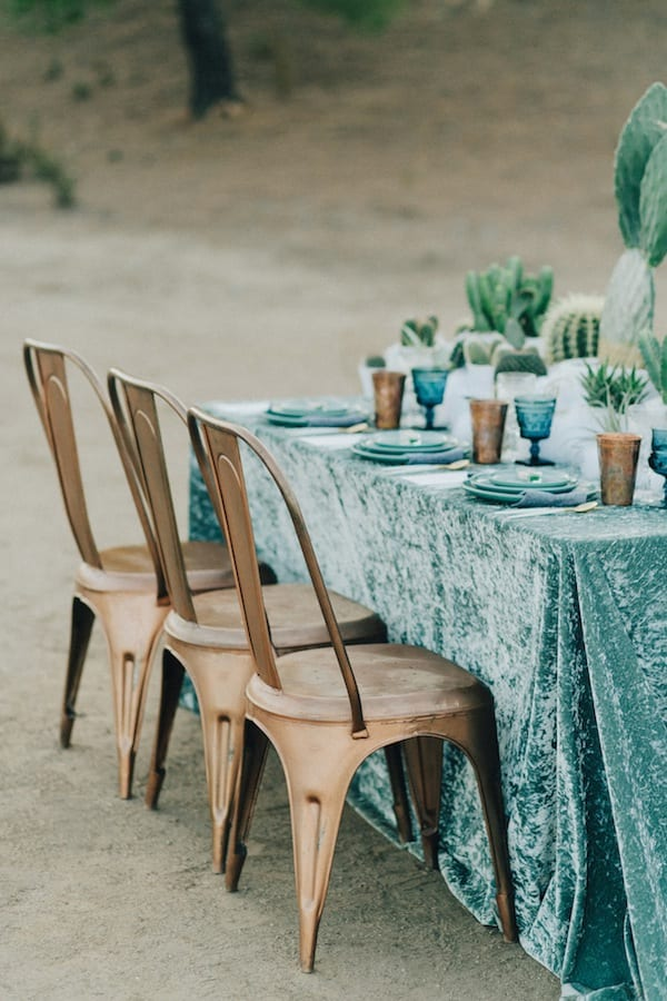 Winter wedding ideas for a table in blue velvet cloth with bronze chairs in the desert, set fully