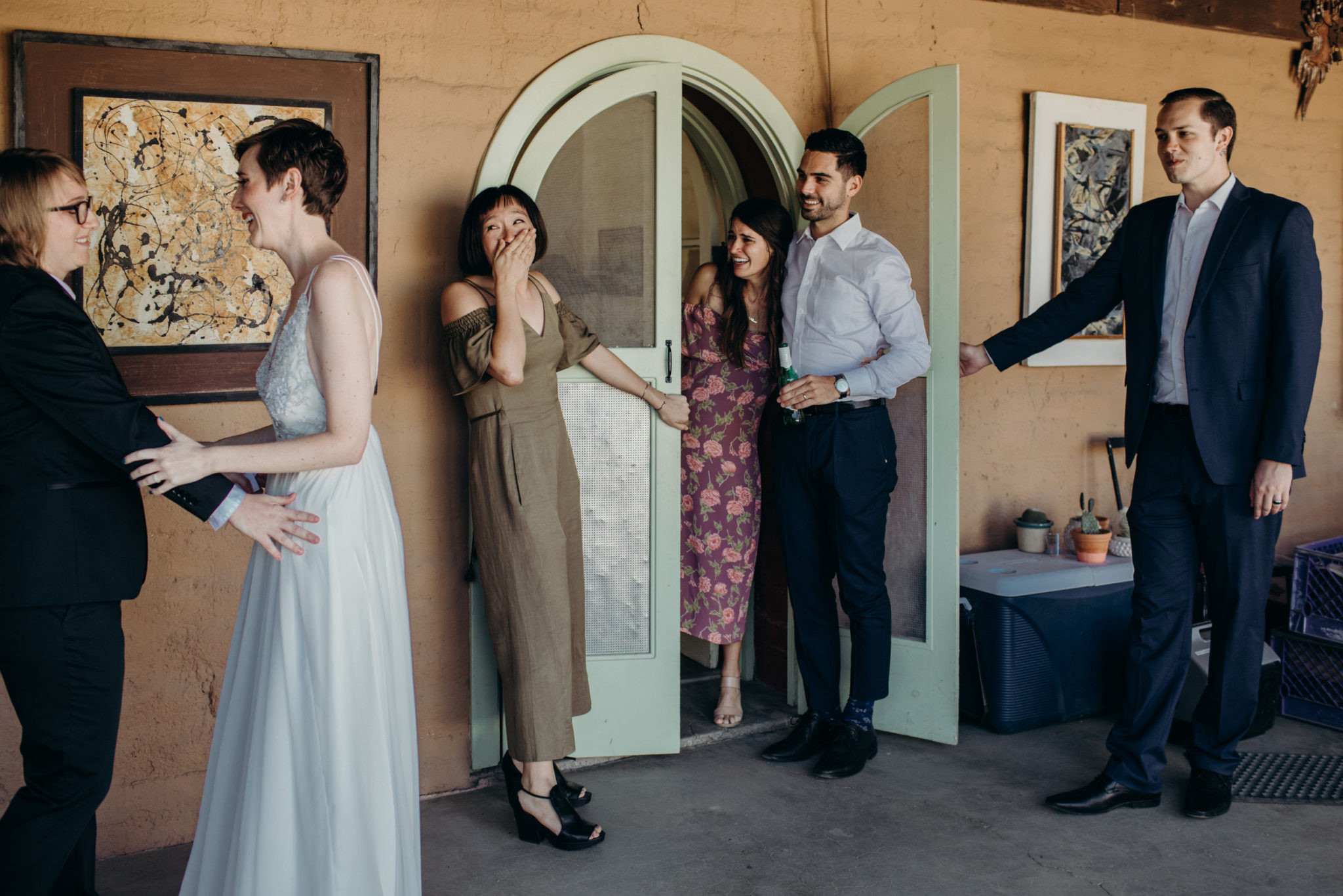 The reaction of several guests to a queer wedding couple experiencing their first look is documented in a photo by Betty Clicker