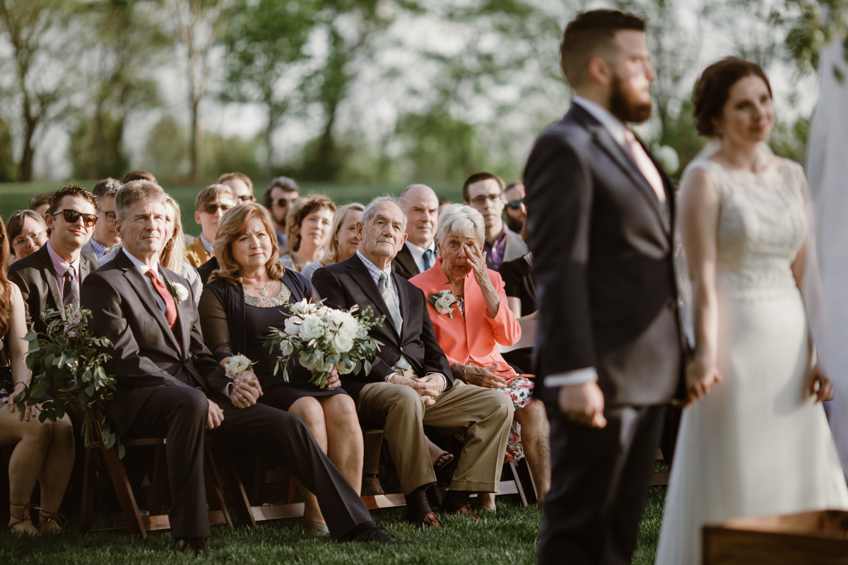 A couple is shown in the foreground during their wedding ceremony as their guests look on, and an elderly woman in a pink suit in the front row wipes away tears in a photo by Betty Clicker