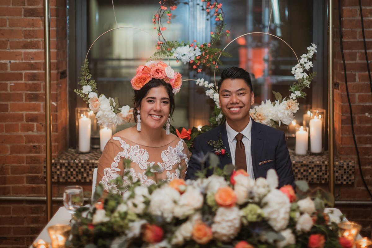 A bride wearing a crown of large salmon-colored flowers and a groom in a blue suit are seated at a sweetheart table behind a pile of matching flowers and look into the camera and smile in a photo by Betty Clicker