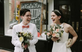Queer wedding couple in white jacket and pink bow tie and white wedding dress both hold bouquets and laugh excitedly in a photo by Betty Clicker