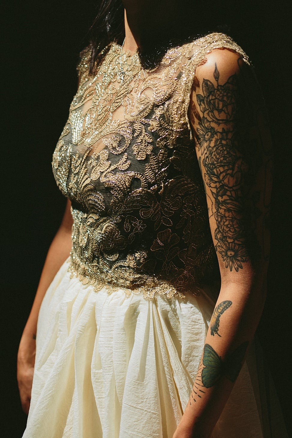Winter wedding ideas for a medium close up of bodice of woman wearing gold and white dress