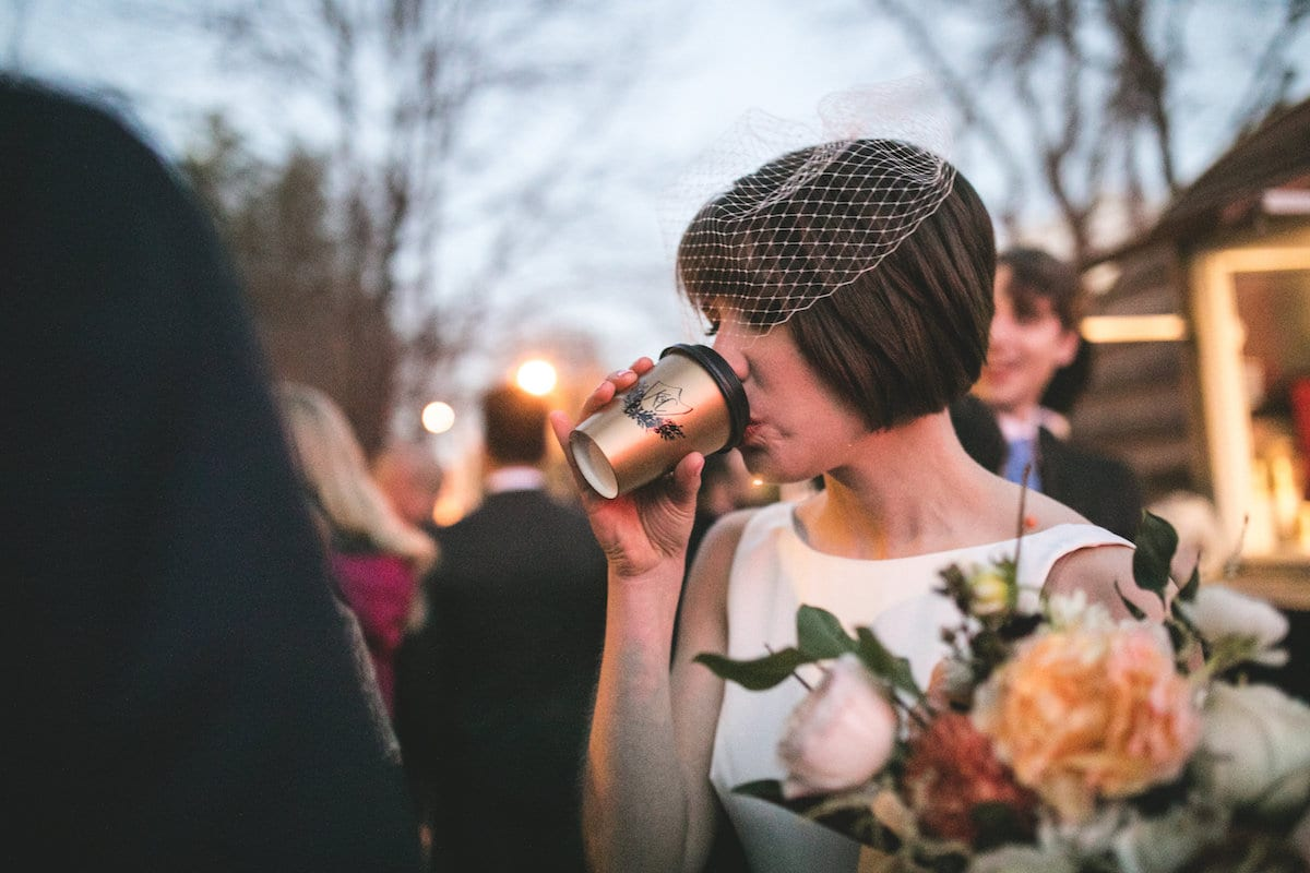 Winter wedding ideas for a sweet treat—Woman drinking hot chocolate wearing fascinator and white dress