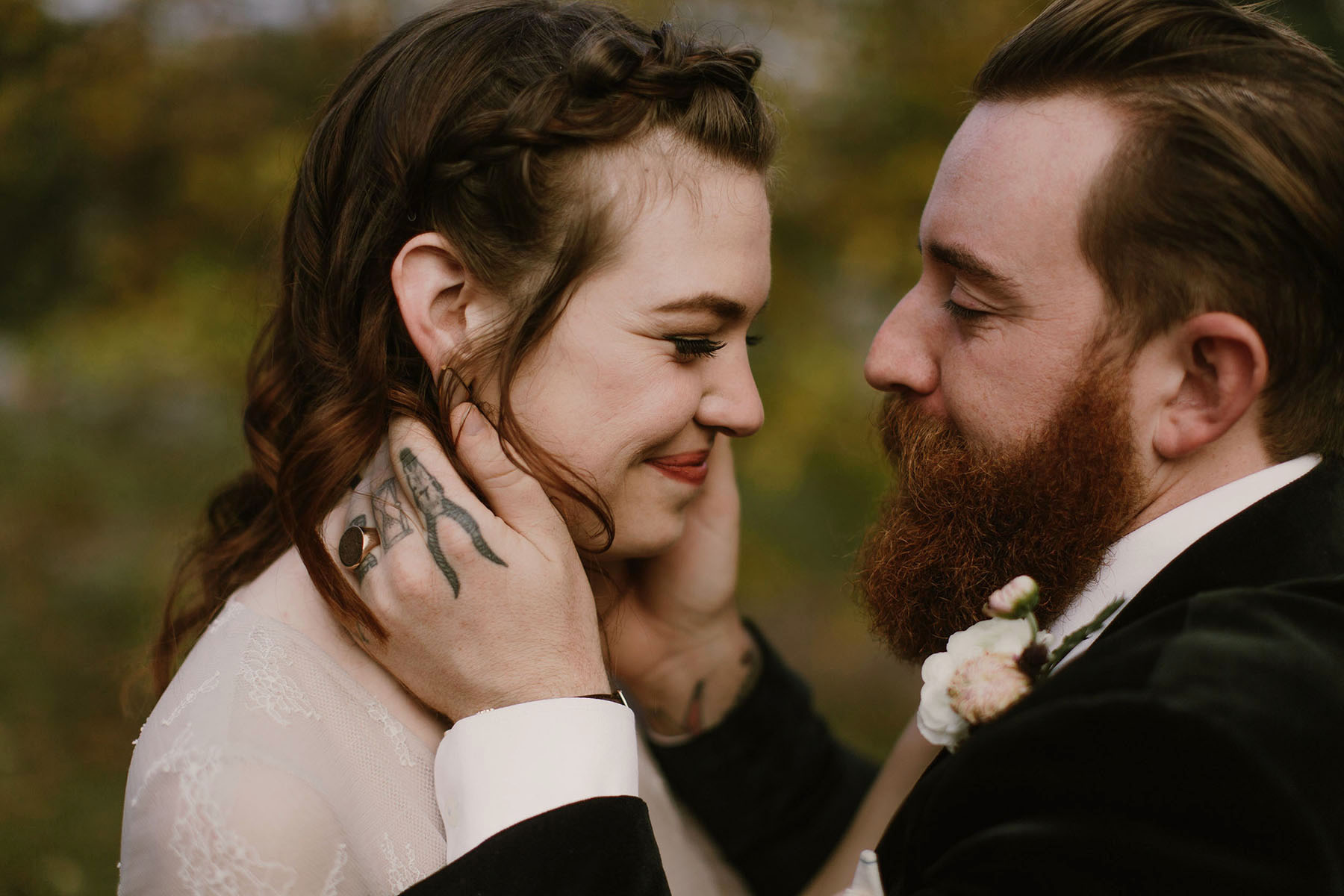 A man with a tux and beard holds the face of a smiling brunette woman in a wedding dress in a Sarah Gormley photo