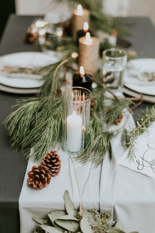 Winter wedding ideas for a winter tablescape of plates, candles, fir foliage and pinecones