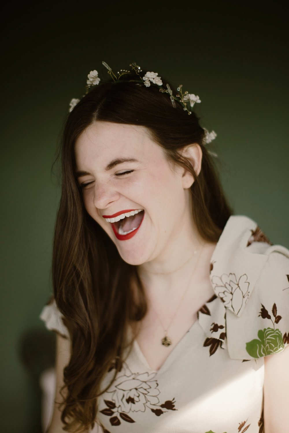A woman in a flower crown and floral print dress with bold red lipstick laughs with eyes closed and mouth open in a Sarah Gormley photo