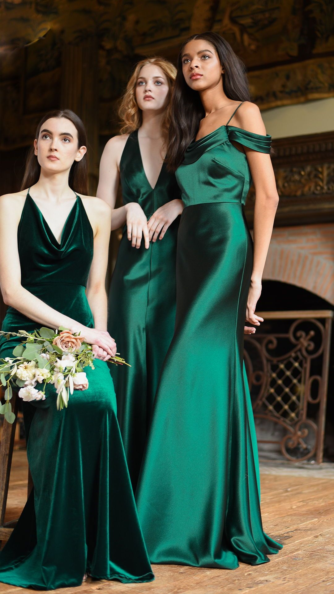Three women wearing dresses in winter wedding colors: dark green dresses, holding flowers