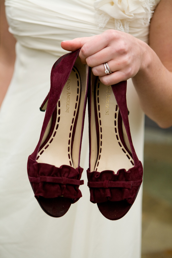Woman holding pair of winter wedding colors burgundy/oxblood velvet heels