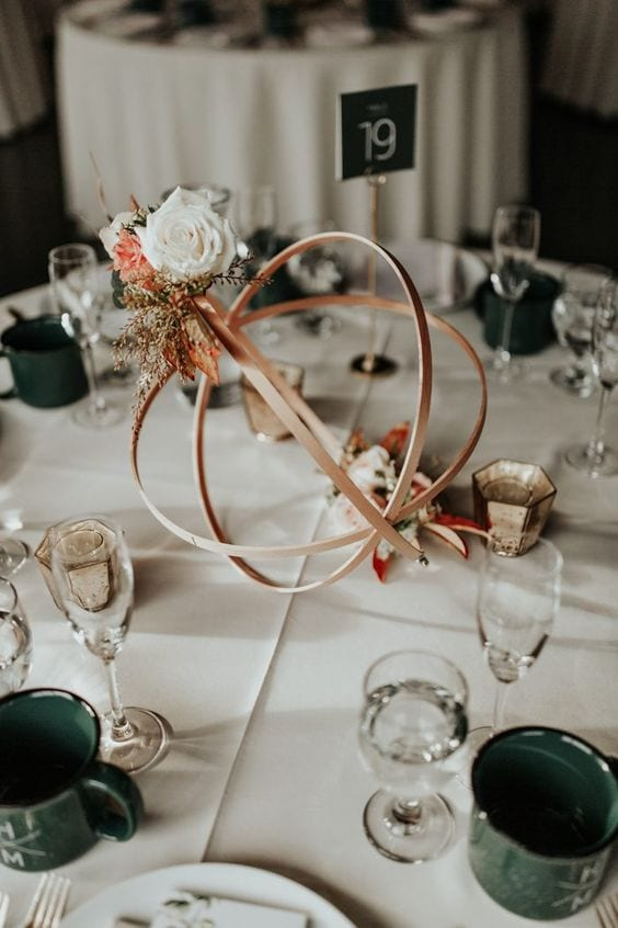 wedding ideas for abstract centerpieces with flowers—a bronze metal orb with coordinating flowers