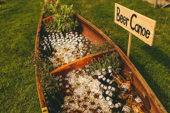 "wedding ideas for beer in a canoe with a yard sign that reads ""Beer Canoe"""