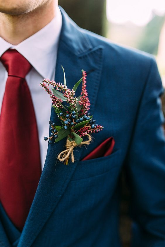 Close up of man in winter wedding colors: a medium blue coat with a dark red tie and coordinating boutonnière