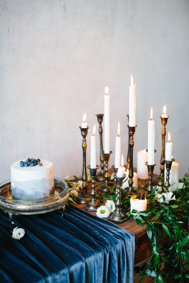 Cake and candles on sideboard with a winter wedding colors indigo velvet tablecloth