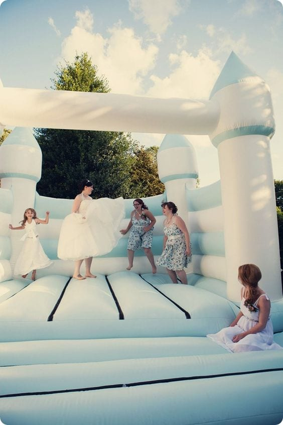 wedding ideas for a bride and bridal party jumping in a light blue and white bouncy castle