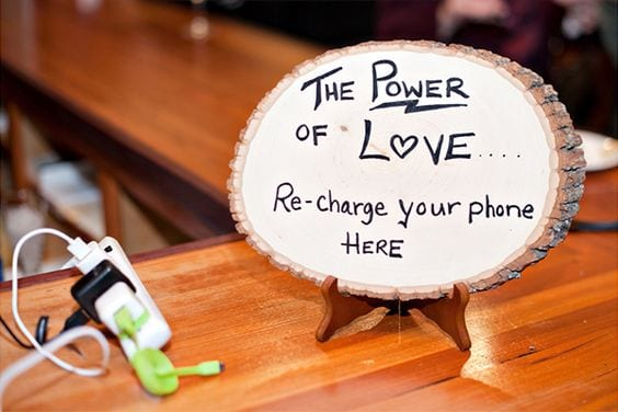 "Wedding ideas for guest convenience—a charging station with a power strip and multiple adapters for phones next to a sign written on a slice of wood that reads, ""The power of love... re-charge your phone here"""