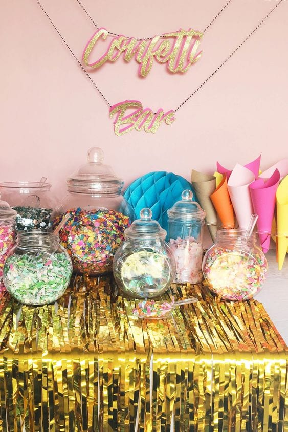 "wedding ideas—a table with jars of confetti and paper cones to fill. A glittery sign above the table reads ""Confetti Bar"""