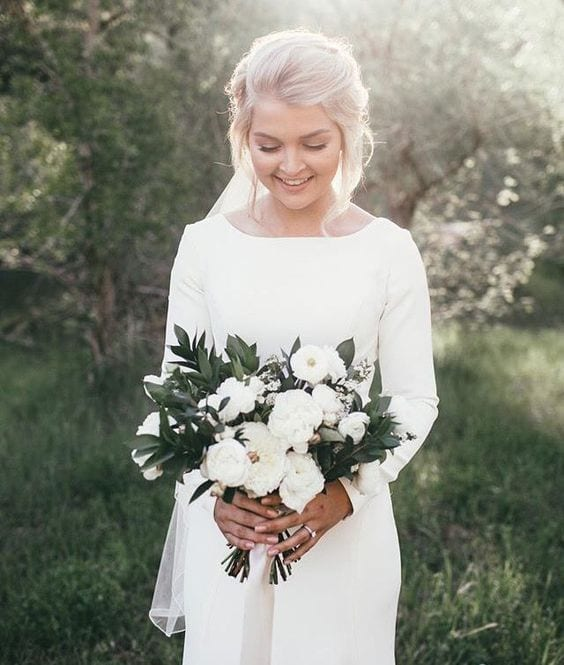 Winter wedding ideas for long-sleeved dress—Blonde woman in white gown holding bouquet