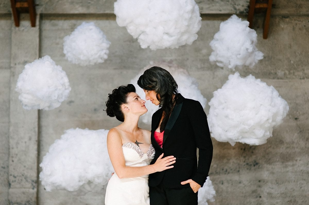 Wedding ideas for a DIY backdrop—two women in front of clouds suspended with invisible wire