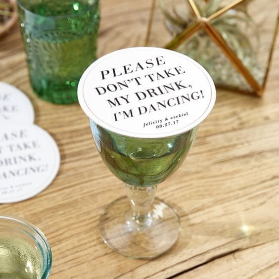 "wedding ideas for coasters—Drink Saving Coaster that reads ""please don't take my drink, I'm dancing"" with the couple's names and wedding date. It sits on a green and clear glass goblet"