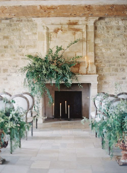 Winter wedding ideas for altar decorations—Fireplace and rows of chairs in room adorned with green arrangements