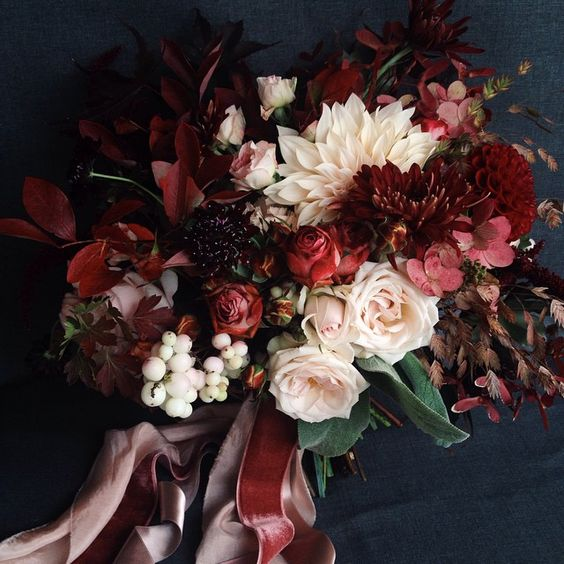 Bouquet in winter wedding colors: red, burgundy, white, and cream on a navy background, with velvet ribbons